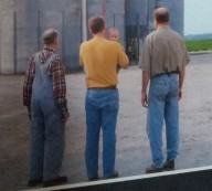 A photo that hangs in the office of Grandpa, me, my son, and Dad in the barn lot.